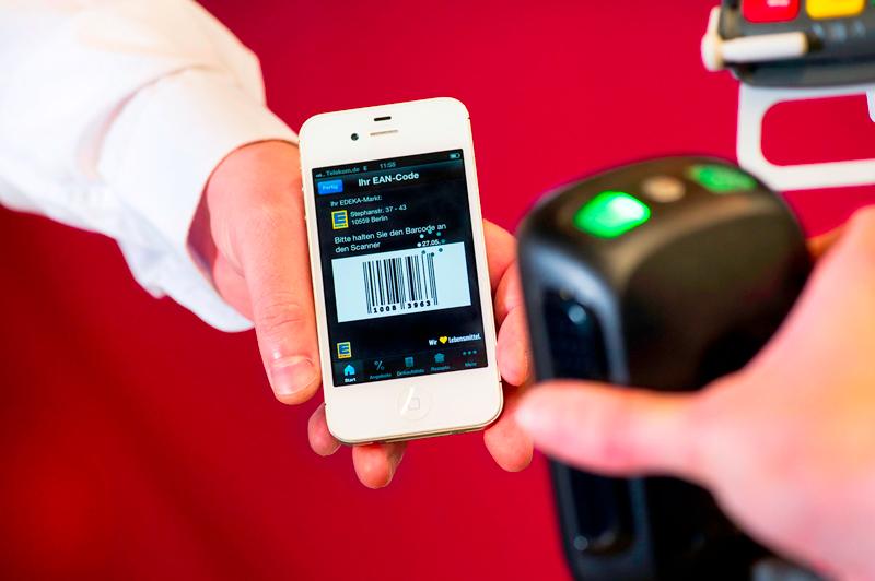 Smartphone mit Strichcode auf dem Display wird vor einen Kassenscanner gehalten.